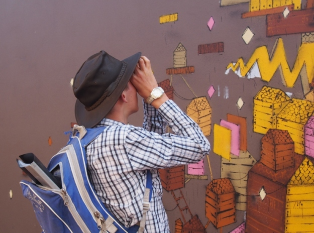 Keon examining a detail of a mural by Kyle Hughes-Odgers