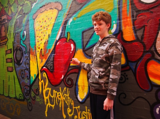 Daniel McLachlan with coffee shop mural - a real dance of colours and shapes by Angie Pannone - at The Pantry on Prince, Busselton