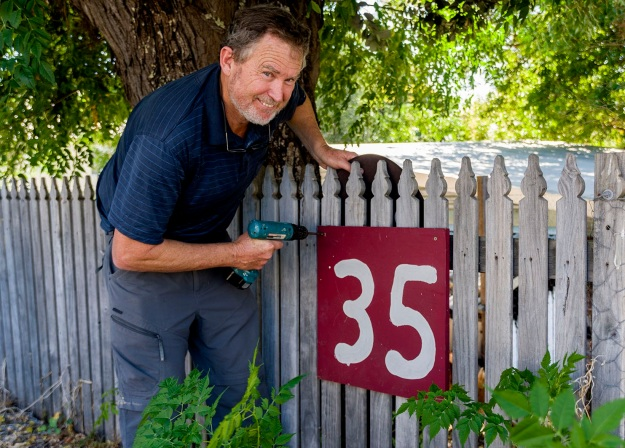 Simon Hemsley affixes the sign for 35 Picton Crescent. Photo by Rob Cox