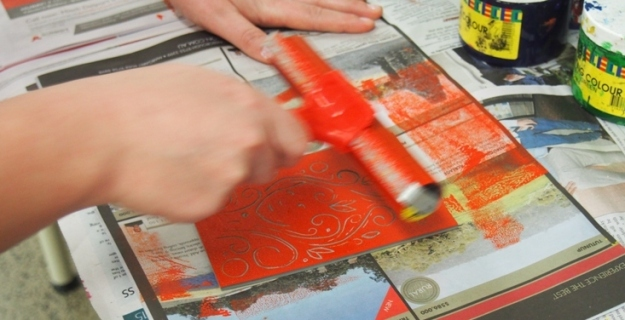 Hands of Eliza Daebler rolling beautiful colour on her lino before making her print
