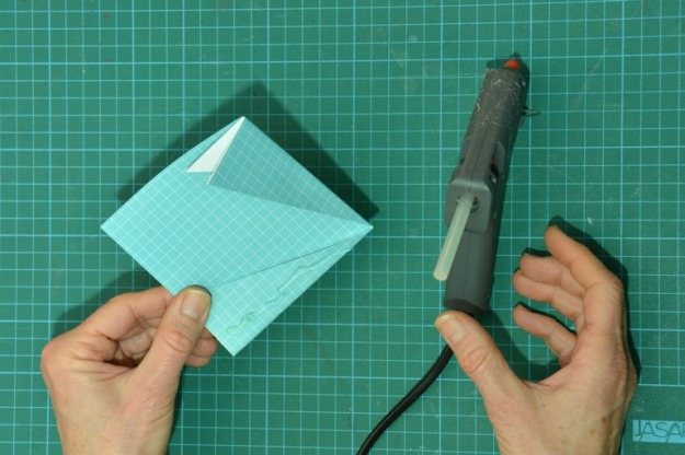 Folded paper with glue applied to one flap. Photo by Carensa Watts