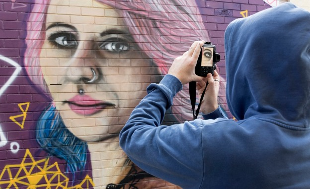 Sam Everitt with Dee Mosca mural. Image by Rob Cox