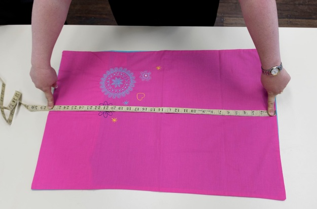 Checking the size. This pillowcase will make a medium-sized dress when complete. Photo by Rob Cox